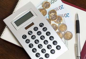 Calculatrice et pièces de monnaie sur une table